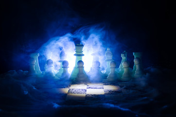 Chess in the snow. winter concept. Christmas or New Year present on a chessboard with Santa Claus on a dark background. Copy space.