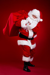 Santa Claus carrying big bag , isolated on red  background