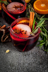Traditional winter and autumn drinks. Christmas and Thanksgiving Cocktails. Mulled wine with orange, apple, rosemary, cinnamon and spices on a dark stone background, copy space