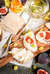 Sandwiches with ricotta or cream cheese, ciabatta, fresh figs, pears, grape, walnuts and honey on wooden board over dark grey stone table, with wine glass copy space, top view
