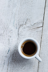 Top view of coffee cup on white wooden background with space for text