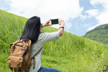 Asia woman traveler with backpack use mobile phone take a photo of landscape mountain view,Travel wanderlust concept,mock up screen mobile.