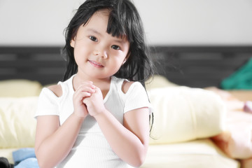 Asian children cute or kid girl smile with hold hand and pray or beg for peaceful world with wear white clothes in bedroom at home