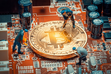 macro miner figurines working on a bitcoin on computer motherboard