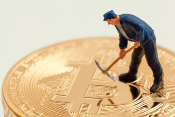 macro miner figurine on bitcoins. cryptocurrency concept