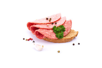 Salami smoked sausage slices isolated on white background with herbs