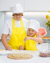 Boy with a mother in the kitchen sprinkles flour dough