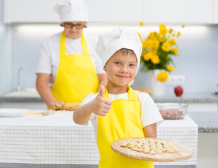 boy in the kitchen holds a cooked dumplings in his hands and shows a thumbs-up, mom in the background