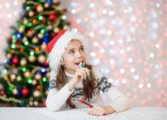 girl in red christmas hat thinking what to write in a letter to Santa Claus. Space for text