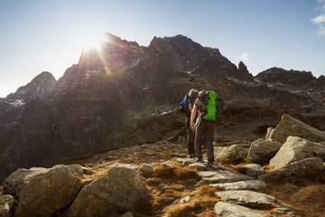 Mountain trekking - two tourists walking towards a mountain