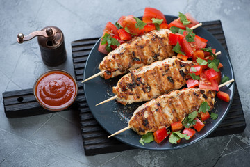 Plate with chicken lula kebabs and fresh vegetables on a black wooden serving board, grey stone surface, studio shot