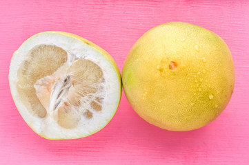 pomelo on a pink background close up. concept vitamins