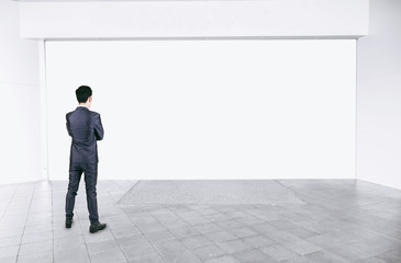 Businessman in black suit standing in empty interior with mock up white space