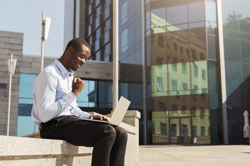 African-american businessman working with laptop outdoors