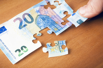 Saving concept: hand putting a piece on a 20 euro puzzle