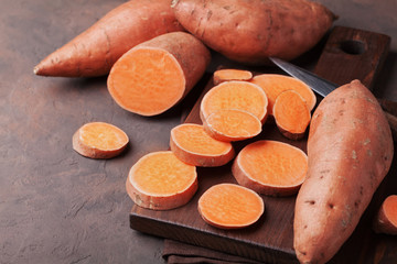 Organic sweet potatoes whole and sliced on wooden kitchen board.