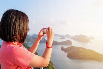 Woman tourist on peak viewpoint of Ko Wua Ta Lap island use camera take photos at beautiful nature landscape during sunrise over the sea in Mu Ko Ang Thong National Marine Park, Surat Thani, Thailand