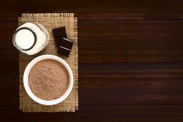 Cocoa or chocolate drink powder in bowl with bottle of milk on the side, photographed overhead with natural light (Selective Focus, Focus on the chocolate powder)