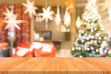 Wooden board empty table top on of blurred background. Perspective brown wood table over blur christmas tree and fireplace background, can be used mock up for montage products display or design layout