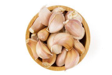 Garlic in wooden bowl top view isolated white background