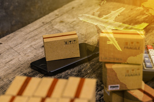 Light brown small boxes and cell phone with a plane flies above world map. For ideas about transportation, international freight, global shipping, overseas trade, regional ,local forwarding.