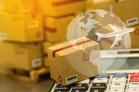 small papers boxes and calculator with a plane flies above world map. For ideas about transportation, international freight, global shipping, overseas trade, regional ,local forwarding.