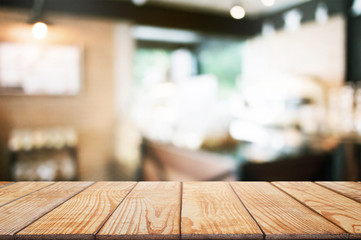 empty wooden desk over blurred coffee shop cafe background