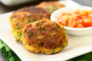 Zucchini, couscous and parsley fritters with tomato and onion dip on the side, photographed with natural light (Selective Focus, Focus in the middle of the first fritter)