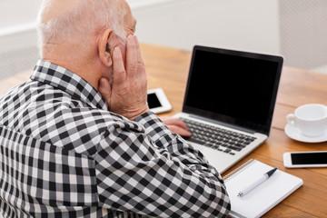 Senior man using laptop with blank screen mockup