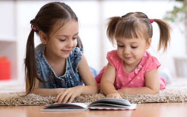 Child girl reading book with little sister at home