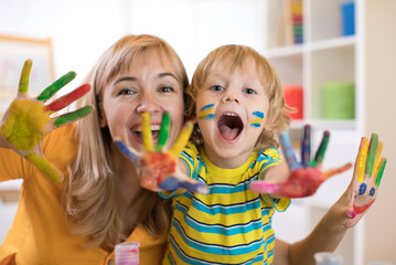 Smiling child boy and his mother having fun and showing hands painted in colorful paints