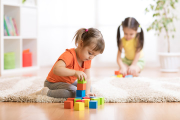 Children toddlers girls playing toys at home, kindergarten or nursery