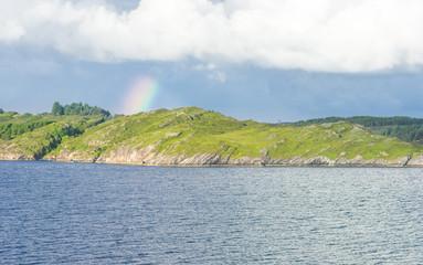 Fjordlandschaft an der Küste mit Regenbogen
