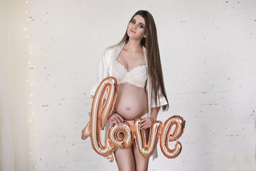 "Expecting future mother  holds golden air balloon ""LOVE"""