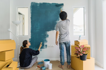 Young asian couple painting interior wall with paint roller in new house