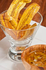 Baked plantain with mojo / Baked plantain slices with a wood bowl of  mojo on a square, white plate on a wood serving board