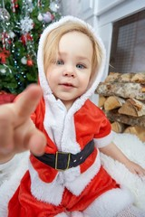 portrait of cute happy baby girl in red santa hat and dress