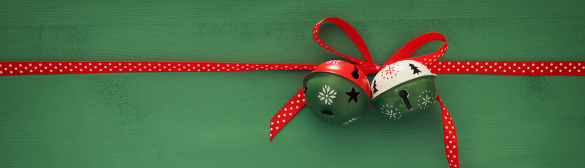 Christmas background with red silk traditional ribbon and jingle bells.
