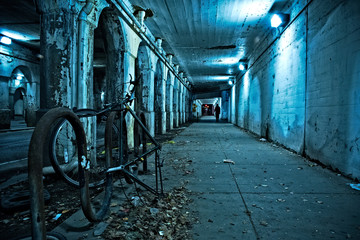 Wall Mural - Gritty dark Chicago city street under industrial train bridge viaduct tunnel with bicycle and person at night.