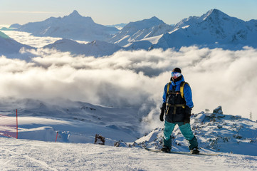 A professional snowboarder with a backpack stands on the snow high in the mountains against the background of low clouds and the Caucasus mountains during the setting sun