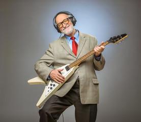Senior man playing electric guitar