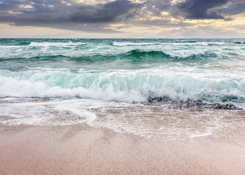 seascape in stormy weather at cloudy sunrise. green waves crashing on golden sand of the beach