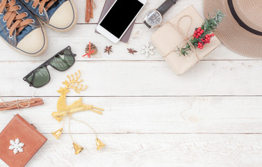 Table top view aerial image of accessories to travel on Merry Christmas & Happy New Year trip background concept.All object on modern rustic white wooden at home office desk studio.Free space for text