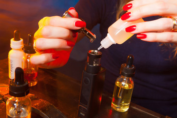 The girl is running a liquid with an electronic cigarette. Liquids for Vape.