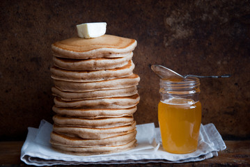 Homemade Whole Wheat Pancakes with honey on a brown wooden background