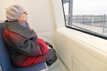Пожилая женщина в первом вагоне поезда метро, беспилотное, автоматизированное управление