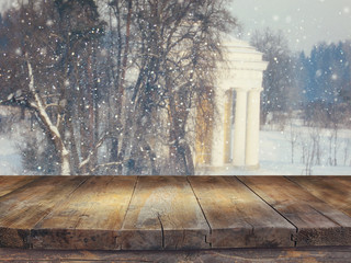Empty wooden table in front of dreamy and magical winter landscape background. For product display montage.