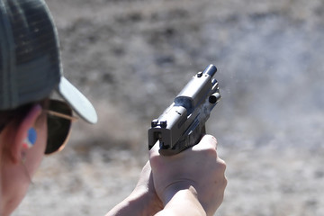 9mm shell casing being ejected after firing from a semi-automatic handgun