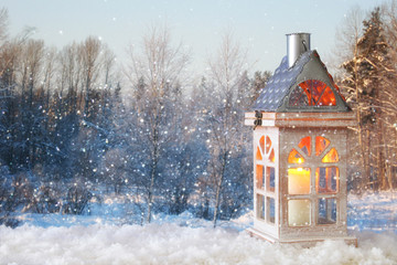 Wooden old house with candle over the snow and blurry magical winter landscape background.