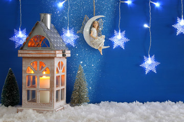 Christmas trees, old lantern, snowflakes silver garland light, fairy on the moon over the snow and blue background.